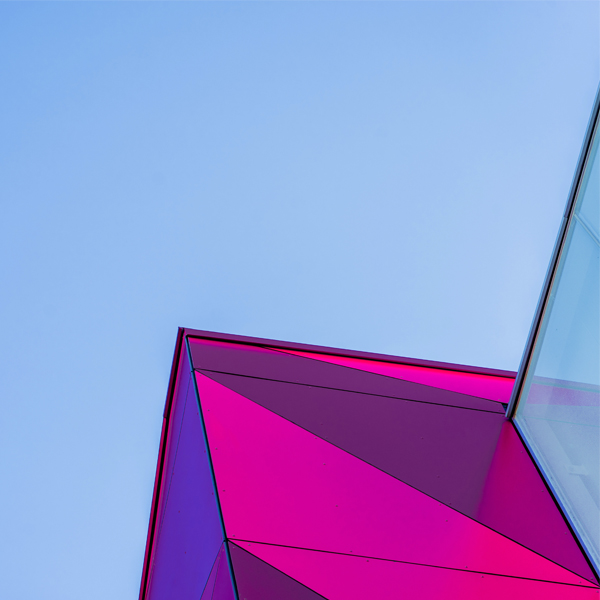 Pink glass wall building under the blue sky