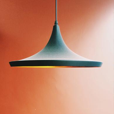 A Green lamp over an orange wall