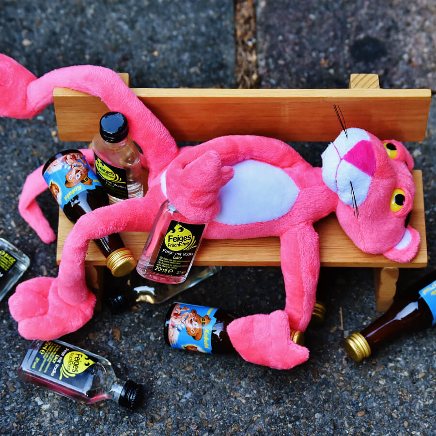 Pink panther lying on a wooden bench drinking