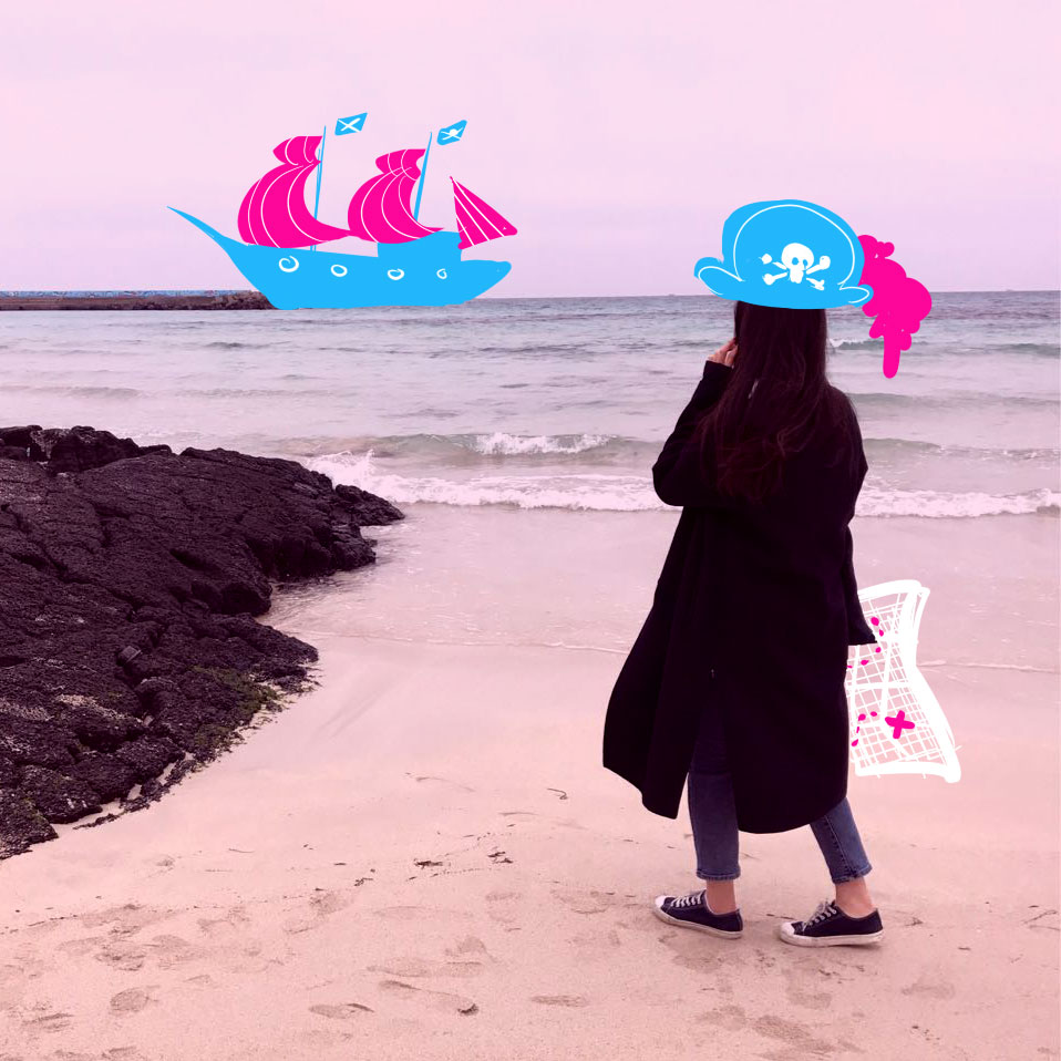 A girl with an illustrated pirate hat, holding a treasure map looking at a ship