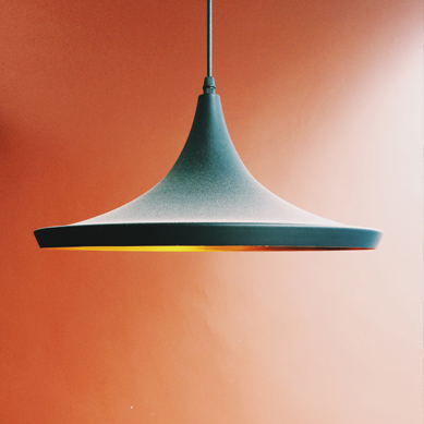 A Green lamp over an orange wall