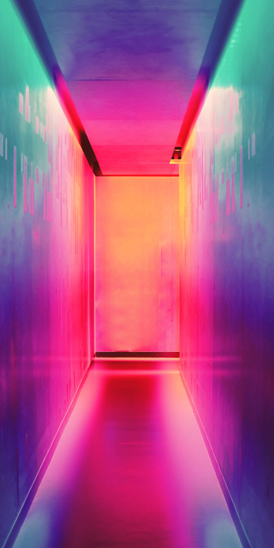 A corridor illuminated by purple, pink, green orange neon lights