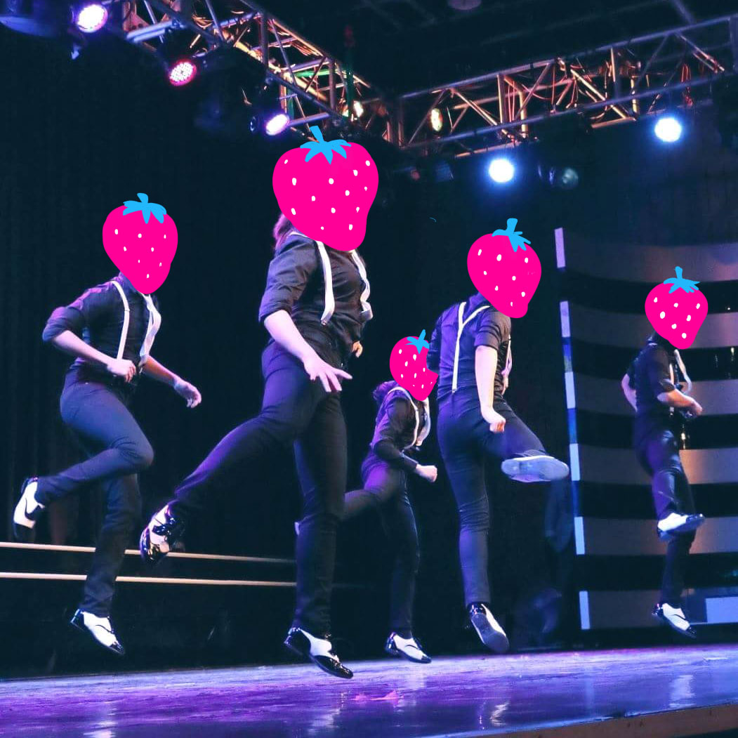 Dancers with illustrated strawberry heads performing on the stage